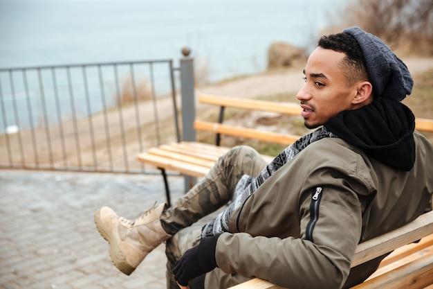Afrikaanse man met hoed en sjaal zittend op een bankje