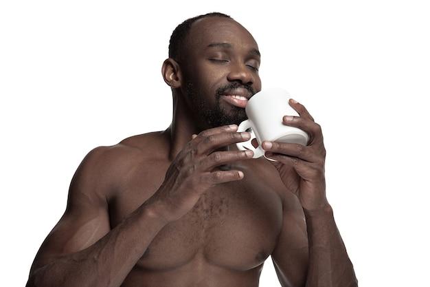 Afrikaanse man met witte kopje thee of koffie, geïsoleerd op witte studio achtergrond. close-up portret in minimalistische stijl van een jonge naakte gelukkig afro man