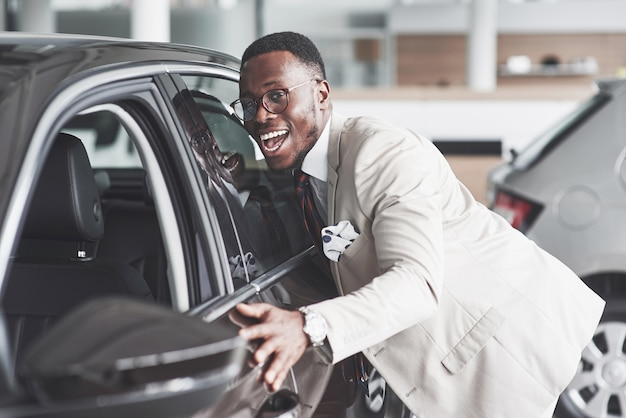 Afrikaanse man op zoek naar een nieuwe auto bij de autodealer.