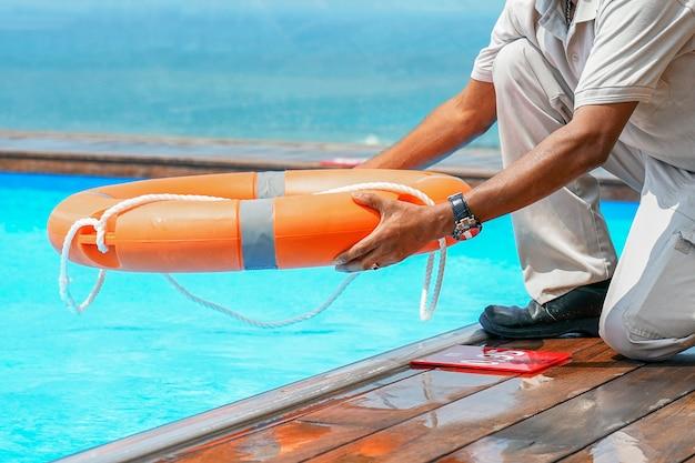 Afrikaanse man redder met reddingsboei in zwembad. afrikaanse hotelmedewerker gooit een reddingslijn naar de mens die het zwembad verdrinkt. redding van een zinkende persoon. vaste voetring in zwembad