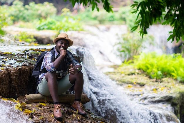 Afrikaanse man reiziger ontspannende vrijheid bij waterval