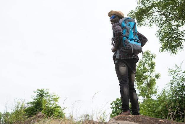 Afrikaanse man reiziger permanent op de top van de berg en met rugzak