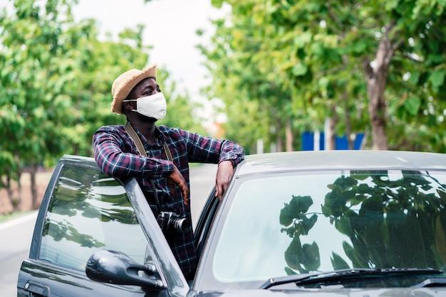 Afrikaanse man reiziger staat in de buurt van auto freelancen op de weg met slijtage gezichtsmasker en camera te houden.