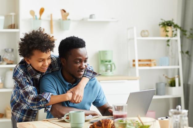 Afrikaanse man zit aan de tafel en werkt op laptop met zijn zoon hem omhelzen ze zijn in de keuken
