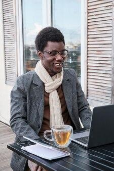 Afrikaanse man zit aan tafel voor laptop en praat online terwijl hij op terras zit