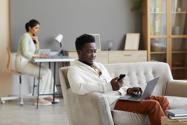 Afrikaanse man zittend op de bank met laptop en het gebruik van mobiele telefoon met vrouw die in de muur thuis werkt