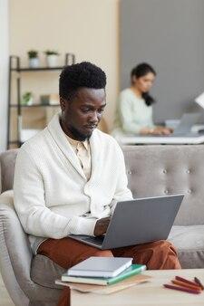 Afrikaanse man zittend op de bank voor de tafel met boeken en typen op laptop die hij thuis online leert