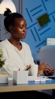 Afrikaanse manager die online spreekt met externe collega's die een laptop gebruiken