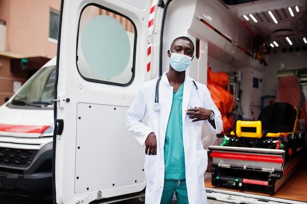Afrikaanse mannelijke paramedicus in beschermend medisch masker dat zich voor ambulanceauto bevindt
