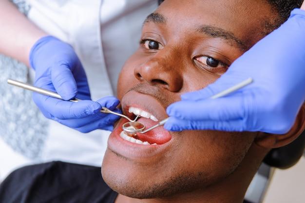 Afrikaanse mannelijke patiënt die tandbehandeling in tandkliniek krijgen