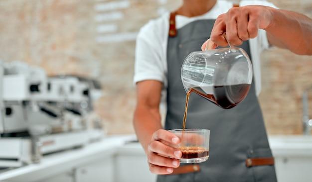 Afrikaanse mannelijke professionele barista in schort bereidt koffie in de cafetaria.