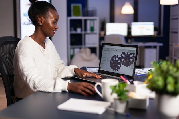 Afrikaanse mechanische ontwerper die 's avonds laat op de computer werkt en overuren maakt om het project af te maken