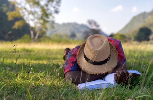 Afrikaanse mens die en na het lezen van een boek op het gras ligt slaapt.