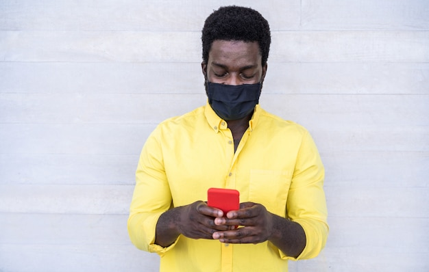 Afrikaanse mens die mobiele telefoon met behulp van terwijl het dragen van gezichts beschermend masker openlucht