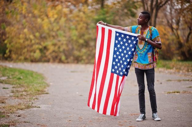 Afrikaanse mens in het traditionele overhemd van afrika op de herfstpark met de vlag van de vs