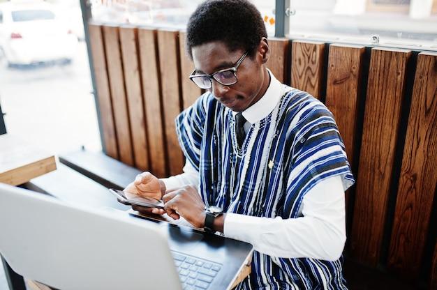 Afrikaanse mens in traditionele kleren en glazen die achter laptop bij openluchtcaffe zitten met telefoon en zijn horloges bekijken