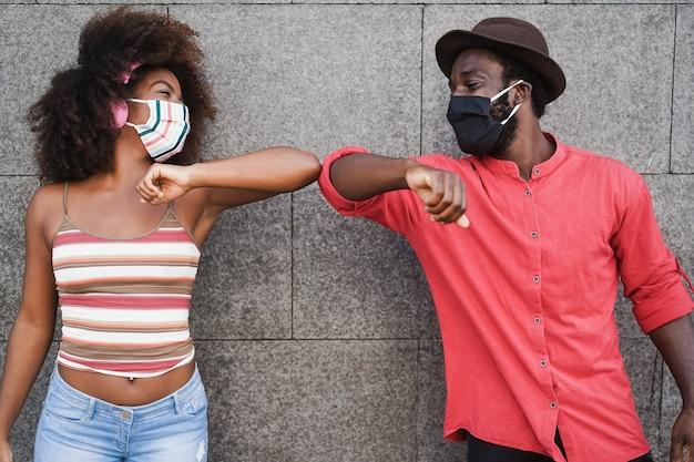 Afrikaanse mensen die gezichtsmaskers dragen terwijl ze hun ellebogen stoten in plaats van te groeten met knuffels - focus op gezichten