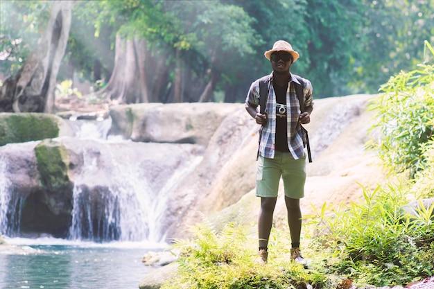 Afrikaanse mensenreiziger met rugzak die en vrijheid bevinden zich ontspannen bij waterval