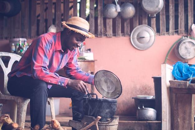 Afrikaanse mensenzitting om brand te blazen om voedsel te koken