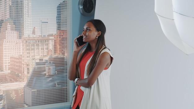 Afrikaanse model spreken met iemand op smartphone.