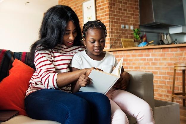 Afrikaanse moeder die haar dochter in het doen van haar thuiswerk helpt