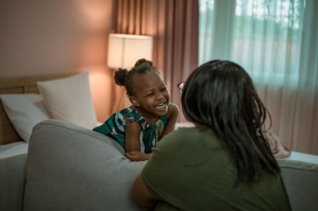 Afrikaanse moeder en dochter samenspelen.