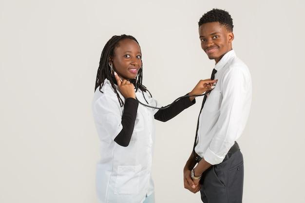 Afrikaanse mooie vrouw in medische jurk met jonge man