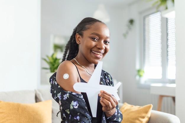 Afrikaanse moslimvrouw lacht na het krijgen van een vaccin, met een papieren vliegtuigje als symbool voor klaar om te reizen. vrouw toont haar arm met verband na vaccinatie.