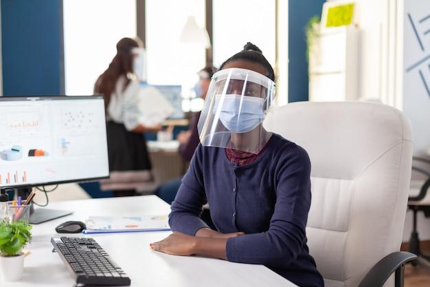 Afrikaanse onderneemster die gezichtsmasker en vizier draagt tegen covid19 die camera bekijkt. multi-etnisch business team dat werkt in een financieel bedrijf met respect voor sociale afstand tijdens wereldwijde pandemie.