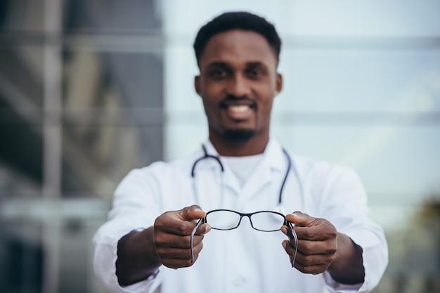 Afrikaanse oogarts biedt een bril aan die in de camera kijkt