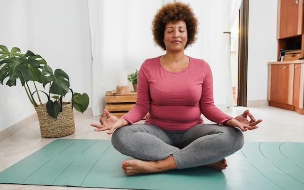 Afrikaanse oudere vrouw die thuis yogasessie doet - focus op gezicht