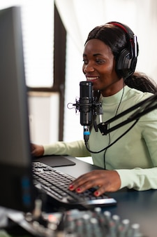 Afrikaanse professionele space shooter-streamer die strategie bespreekt met teamgenoten die in de microfoon praten. virale videogames streamen voor de lol met koptelefoon en toetsenbord voor online kampioenschap.