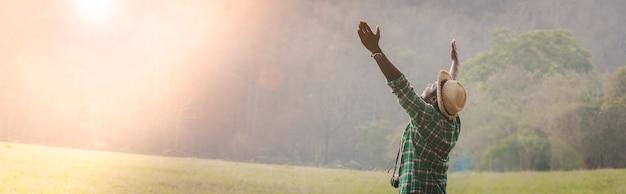 Afrikaanse reiziger man neemt de kracht van de natuur in zich tijdens hun vakanties..avontuurlijk reisconcept