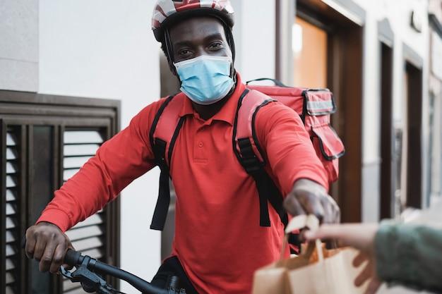 Afrikaanse ruiter die maaltijd met elektrische fiets levert terwijl hij veiligheidsmasker draagt