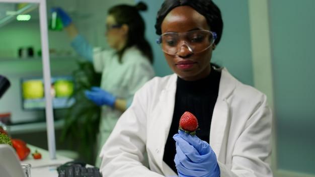 Afrikaanse scheikundige met medische bril kijkt naar aardbei die is geïnjecteerd met chemische bestrijdingsmiddelen
