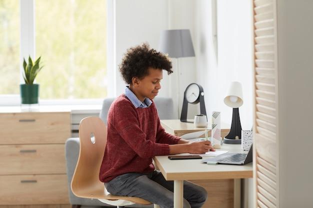 Afrikaanse schooljongen zit aan zijn bureau zijn huiswerk en voorbereiding op de lessen in de kamer thuis