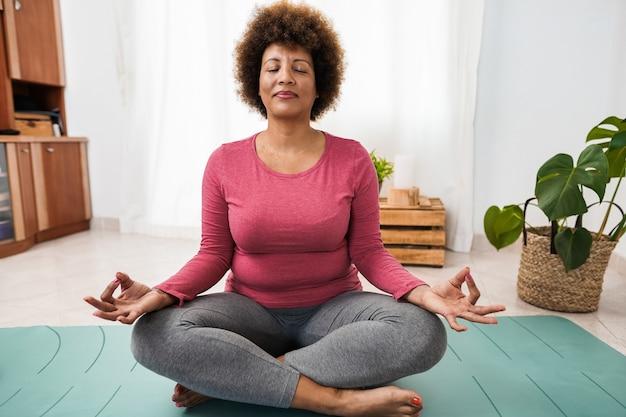 Afrikaanse senior vrouw die yogasessie thuis doet