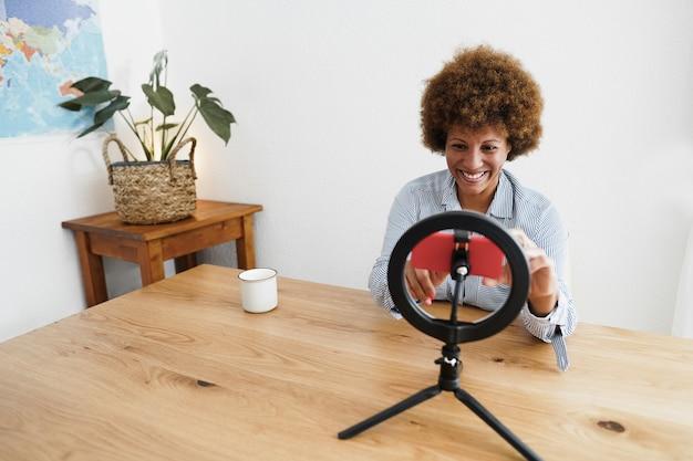 Afrikaanse senior vrouw streaming online met mobiele telefoon camera binnenshuis thuis - focus op gezicht
