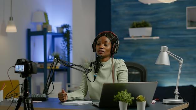Afrikaanse sociale media-vrouw die in laptop kijkt en praat met microfoon die podcast opneemt voor youtube-kanaal met behulp van videocamera. online show on-air productie internet uitzending host streaming live video