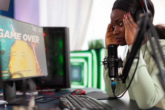 Afrikaanse streamer heeft spijt dat hij een live shooter-game-toernooi heeft verloren dat de tempel aanraakt. professionele gamer die online videogames streamt met nieuwe graphics op een krachtige computer.