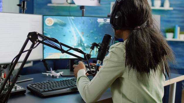 Afrikaanse streamervrouw die met team in hoofdtelefoons spreekt en videospelletjeswedstrijd wint
