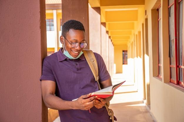 Afrikaanse student die buiten studeert, gezichtsmasker draagt