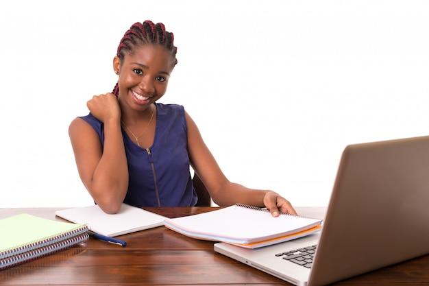 Afrikaanse student die met laptop werkt