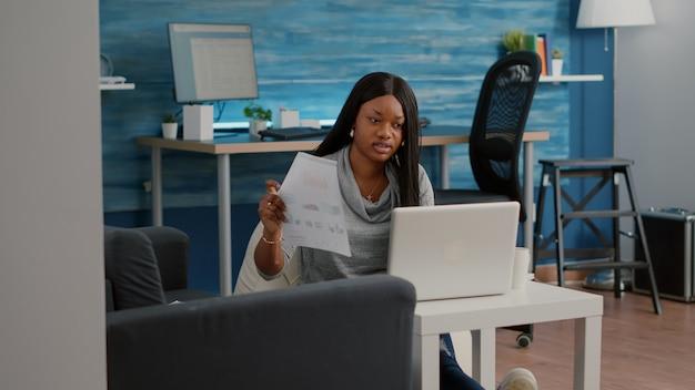 Afrikaanse student die vanuit huis werkt bij marketingstrategie die financiële grafieken typt en presentatie-e-mail schrijft op de computer