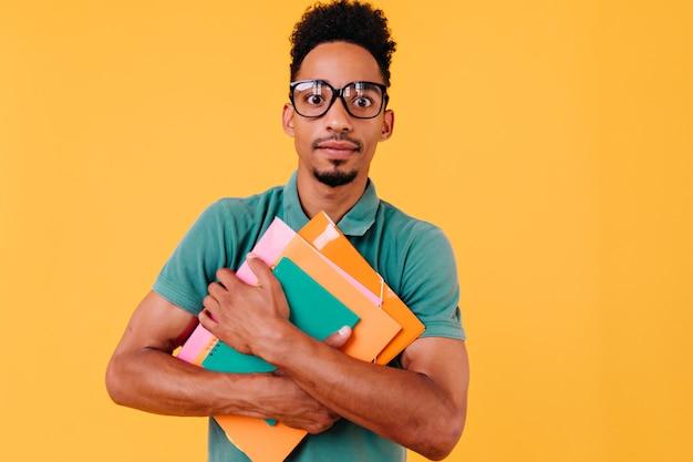 Afrikaanse student in heldere t-shirt poseren met verbaasde gezichtsuitdrukking. zwarte jongen in glazen permanent met boeken en op zoek.