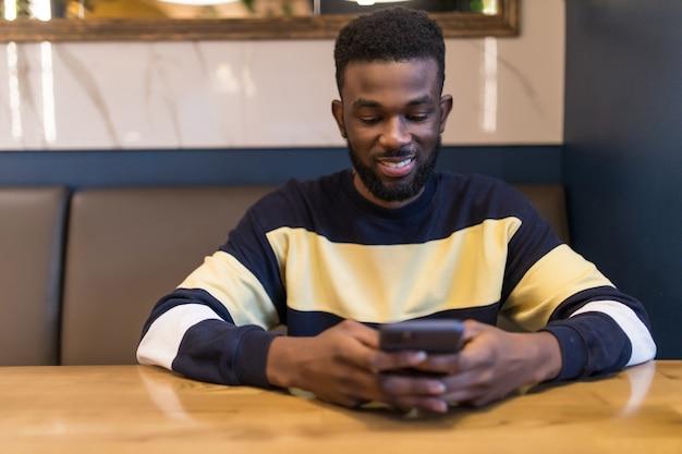 Afrikaanse student met behulp van mobiele telefoon, kijken naar het scherm met ernstige en geconcentreerde uitdrukking terwijl het drinken van koffie in een café