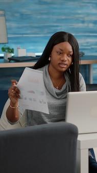 Afrikaanse student werkt vanuit huis bij marketingstrategie en typt financiële grafieken