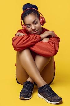 Afrikaanse tiener meisje met dreadlocks in rode windjack luisteren muziek