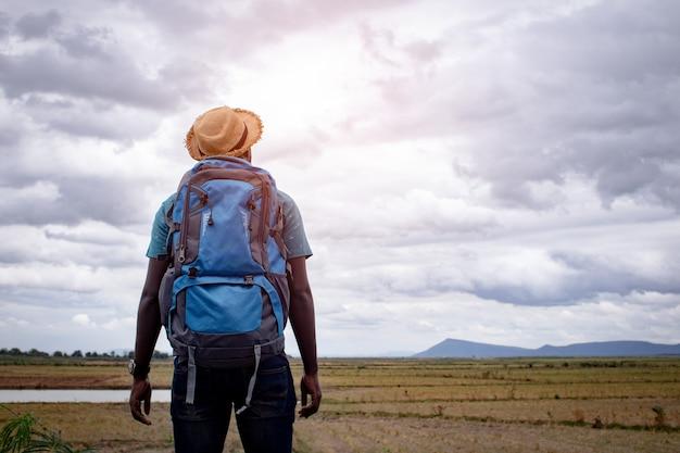 Afrikaanse toeristische reiziger man met rugzak op uitzicht op berg
