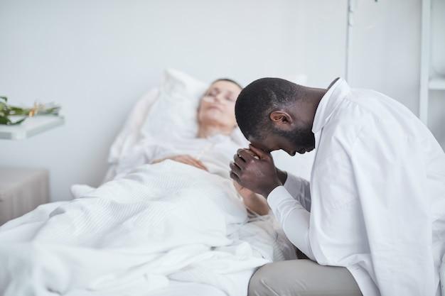 Afrikaanse trieste man die met zijn vrouw voor het ziekenhuisbed zit en zich zorgen maakt over haar gezondheid